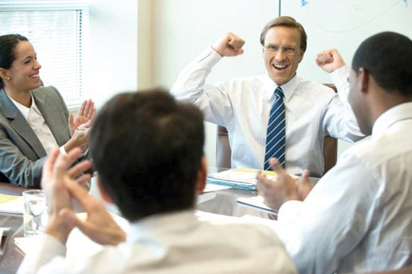 Cheering businesspeople in a meeting
